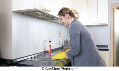 Housewife in rubber gloves spraying detergent over electric...