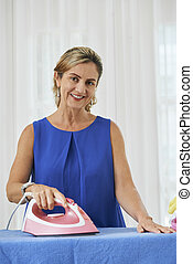 Middle-aged housewife ironing bedsheet and smiling at camera