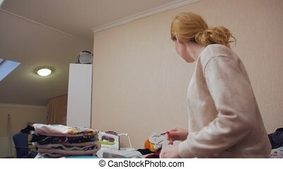 Housewife ironing clothes home interior camera movement