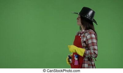 Housewife like a cowboy doing housework spraying detergent against green screen