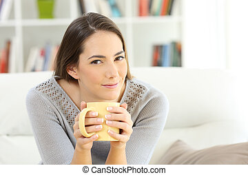 Housewife looking at camera holding a coffee cup