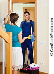 Housewife meeting cleaner at door
