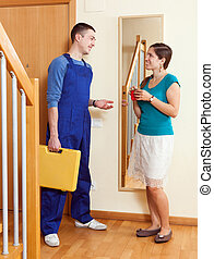Housewife meeting service worker at the door at home