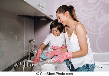 housewife mom in pink gloves washes dishes with her son by hand in the sink with detergent. A girl in white and a child with a cast cleans the house and washes dishes in homemade pink gloves.A child with a cast washes dishes and smiles