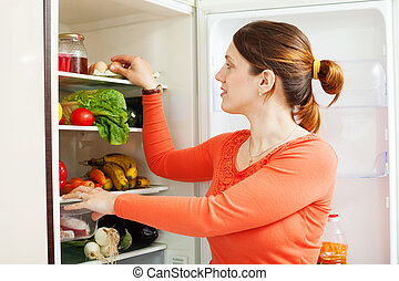 housewife near refrigerator at home kitchen
