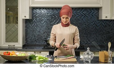 housewife prepares dinner for family cutting vegetables - ...