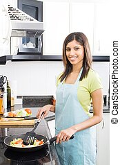 housewife preparing dinner - a housewife smiling while...
