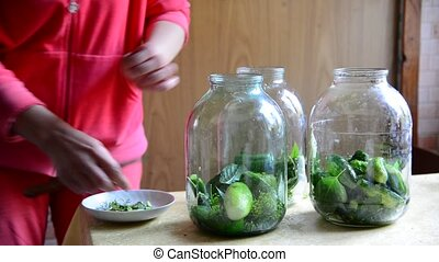 Housewife preparing homemade canned cucumbers for winter