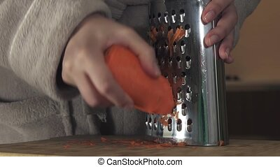 Housewife refines grated carrots in kitchen stock footage...
