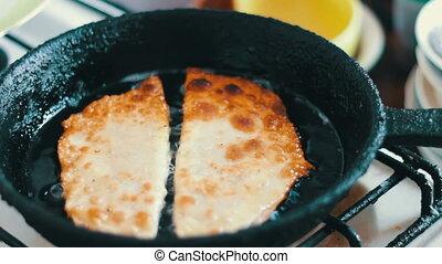 Housewife roasts chebureks in pan - Georgian national dish
