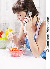 Housewife talking on phone eating fresh salad