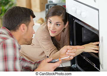 housewife talking to worker near oven in kitchen