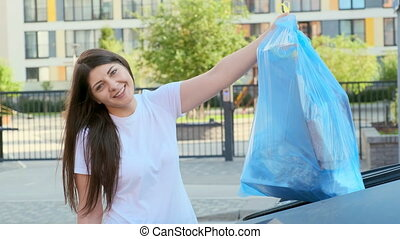 A woman smiles and looks into the camera throws a bag of garbage into the tank near the house.