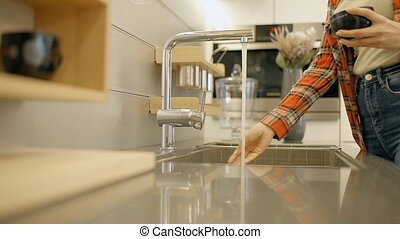 Housewife washing black mug in the kitchen at home. Woman in...