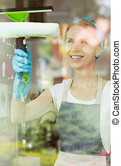 Housewife washing windows with squeegee - Smiling housewife...