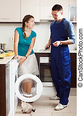 Housewife watching as engineer  repairing washing machine