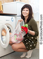 housewife  with laundry bag in kitchen