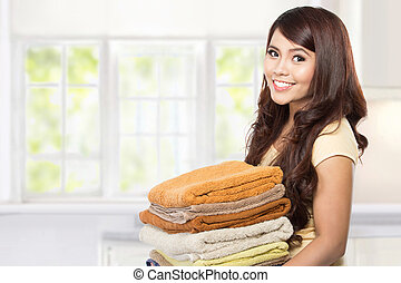housewife with laundry - woman doing a housework holding ...