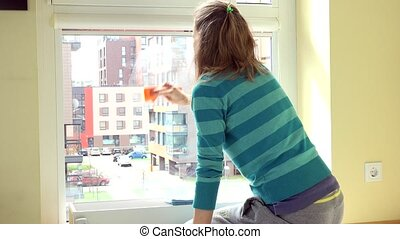 Housewife woman clean window with rag. Flat house living...