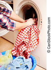 Housewife's hands putting the laundry into the washing machine