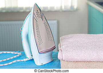 Housework, ironing iron colorful towels on the ironing board.
