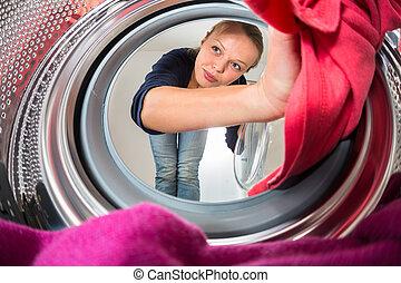 housework:, jonge vrouw , het doen van wasserij