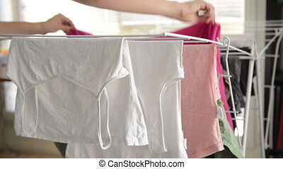 Housework - Woman doing the housework, removing clothes from...