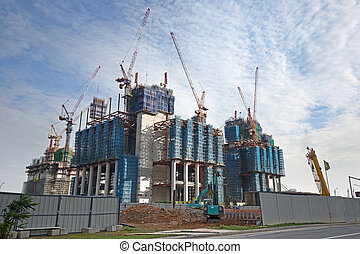 housing development - cranes and scaffolding in an urban...