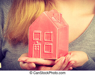 Person holding house model.