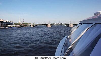 Hovercraft floating rapidly under Brokerage bridge on Neva River in direction of Petropavlovskaya Fortress