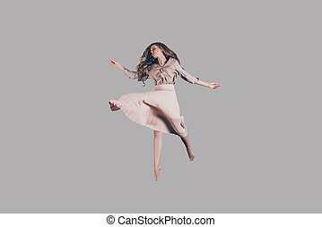 Hovering beauty. Studio shot of attractive young woman in dress hovering in air