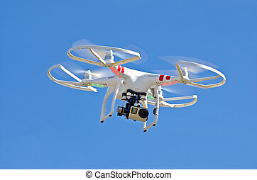 White drone hovering in bright blue sky.
