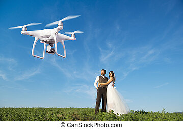 Hovering drone taking pictures of wedding couple in nature -...