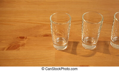 Hovering over 3 shot glasses - Hovering shot of three small...