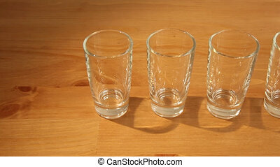 Hovering over many shot glasses - Shot of a row of many...
