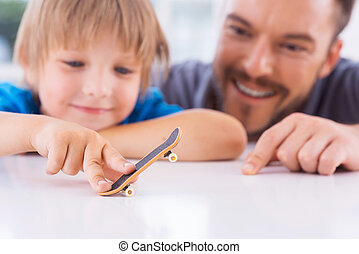 How are you doing like this? Cheerful father looking at his sun playing with fingerboard and smiling