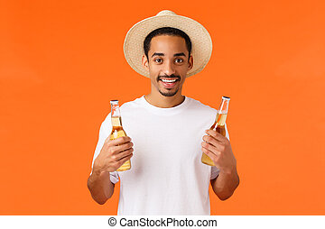 How bout drink. Handsome relaxed and happy smiling african-american man in hat, white t-shirt, holding two bottles of beer, enjoying weekends, relaxing with friends, having party, orange background