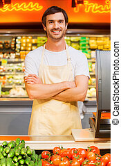 How may I help you? Handsome young cashier keeping arms crossed and smiling while standing at supermarket checkout