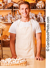 How may I help you? Handsome young man in apron looking at camera and smiling while standing in bakery shop