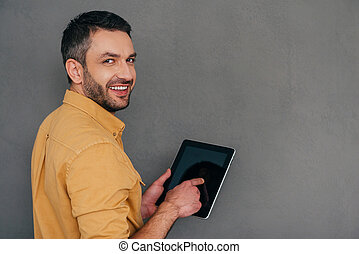How may I help you?  Rear view of handsome mature man holding digital tablet and looking over shoulder with smile while standing against grey background