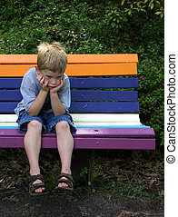 A little boy waiting on a park bench looking very bored.