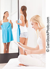 How this dress fits me? Beautiful young woman holding dress and looking at the mirror while another women sitting on the foreground and reading magazine