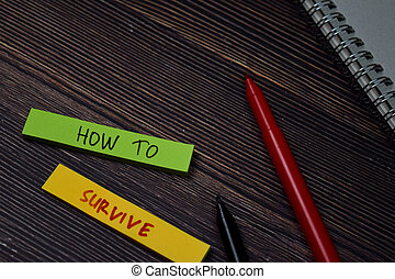 How To Survive write on sticky note isolated on wooden table.
