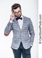 How you doing? Handsome young man wearing suit keeping hand in pocket and looking over his glasses while standing against white background