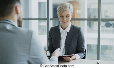 HR businesswoman having job interview with young man in suit and watching his resume application in modern office