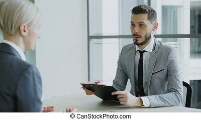 HR male manager having job interview with young woman in suit and watching her resume application in modern office