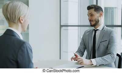 HR male manager shaking hand to female candidate after having job interview in modern office