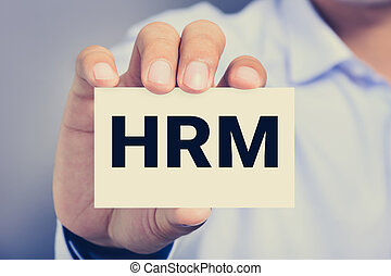 HRM letters (or Human Resources Management) on the card held by a man hand