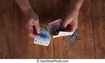 Hryvnia in hand. National Ukrainian currency. - Small...