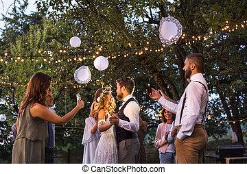 huéspedes, con, smartphones, cautivadora foto, de, novia y novio, en, recepción wedding, exterior.